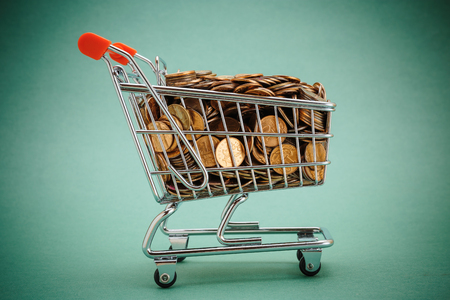 copper background: Shopping trolley with coins on a green background