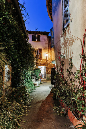cote d'azur: Narrow street with flowers in the old town Mougins in France. Night view Stock Photo