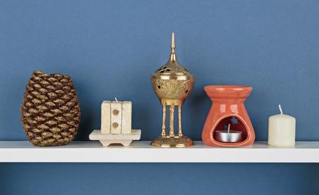 white shelf: Decorative candles on white  shelf on blue wallpaper background
