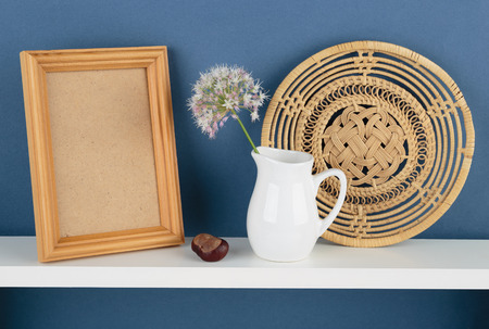 cadre: photoframe and vase with a flower on white  shelf on blue wallpaper background Stock Photo