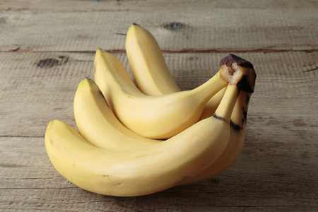 brown banana: Ripe yellow bananas on old wooden boards
