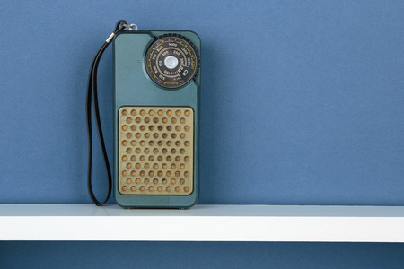 white shelf: Old radio on white  shelf on blue wallpaper background Stock Photo