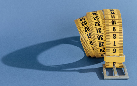 fat and slim: Yellow meter belt slimming on a blue background