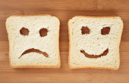 slices of bread: Happy and sad toast breads on a cutting board Stock Photo