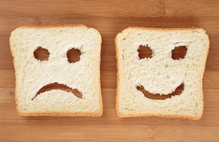 cara triste: panes felices y tristes tostadas sobre una tabla de cortar Foto de archivo