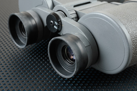 perforation: Binoculars on a metallic background with perforation of round holes