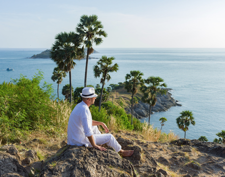 model male: a young man sitting on a rock and looking at the sunset of Phuket Stock Photo