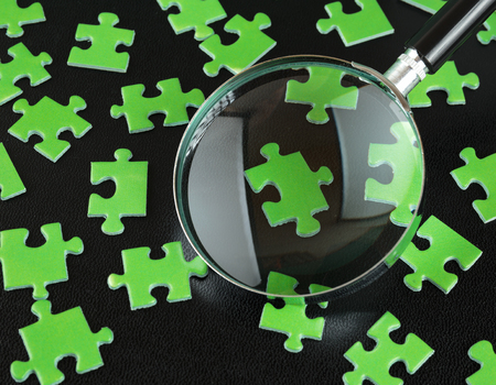 ecomomical: Green puzzles and magnifying glass on a black leather background