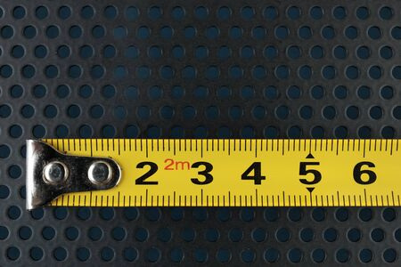 perforation: Measuring tape on a metallic background with perforation of round holes Stock Photo