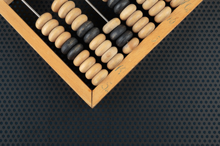 perforation: Old wooden abacus on a metallic background with perforation of round holes