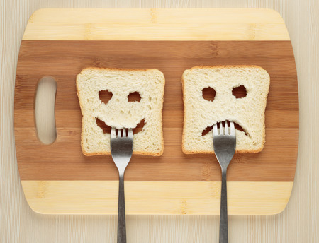 comida rica: Feliz y triste con un tenedor en la boca en una tabla de cortar