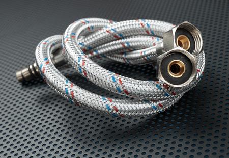 braiding: Water flexible hose in metallic braiding on a dark background Stock Photo