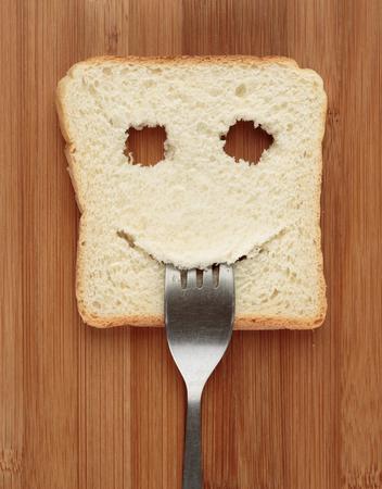 comiendo cereal: Tostada feliz con un tenedor en la boca en una tabla de cortar
