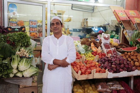 SHARJAH, UAE - NOVEMBER 8, 2013: The seller of fruits in the market. Sharjah is located along northern coast of Persian Gulf on Arabian Peninsula