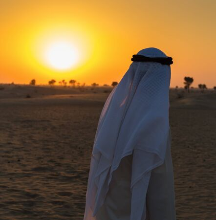 desert: Arab man stands alone in the desert and watching the sunset