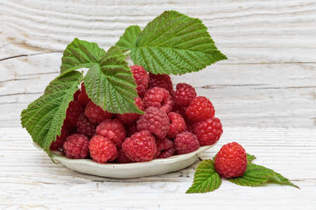 food still: Raspberries in a bowl on a wooden white table