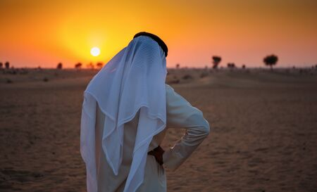 alone: Arab man stands alone in the desert and watching the sunset