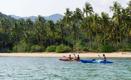 ocean kayak: Koh Chang, Tailandia 28 de marzo 2015; Turistas kayaking en la soleada playa tropical con palmeras Editorial