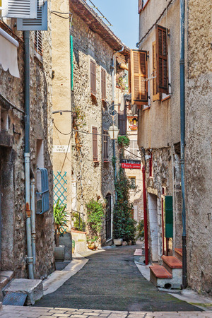cobbled: TOURRETTES-SUR-LOUP, FRANCE - OCTOBER 30, 2014: Narrow cobbled street with flowers in the old village