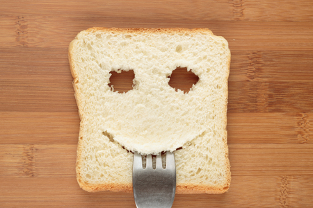 breakfast smiley face: Happy toast with a fork in her mouth on a cutting board