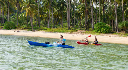 thailand: Koh Chang, Thailand MARCH 28, 2015; Tourists kayaking on sunny tropical beach with palm trees