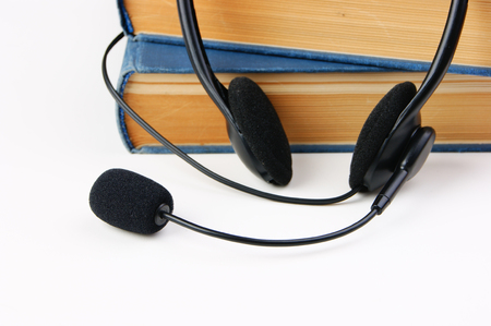 audible: Headphones with a microphone and a stack of books on white background Stock Photo