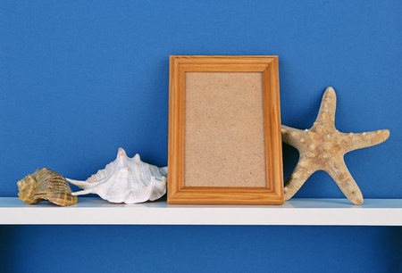 cadre: photoframe with starfish on white  shelf on blue wallpaper background