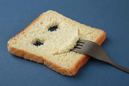 breakfast smiley face: Happy toast with a fork in her mouth on a blue cutting board Stock Photo