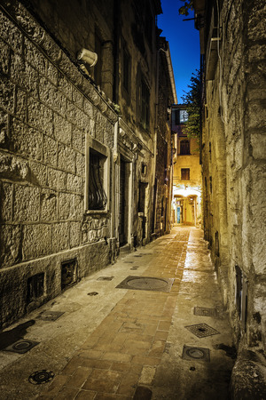 cobbled: Narrow medieval cobbled street in old town Peille at night, France.
