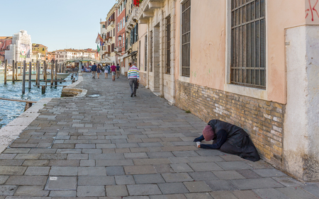 mendicant: VENICE, ITALY - 26 JUNE, 2014: Pauper on a Grand Canal in Venice Italy Editorial