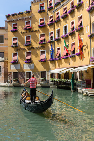 cruise travel: VENICE, ITALY - 26 JUNE, 2014: Gondolier rides gondola. The profession of gondolier is controlled by a guild, which issues a limited number of licenses