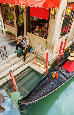 gondolier: VENICE, ITALY - 26 JUNE, 2014: Gondolier on the pier. The profession of gondolier is controlled by a guild, which issues a limited number of licenses Editorial