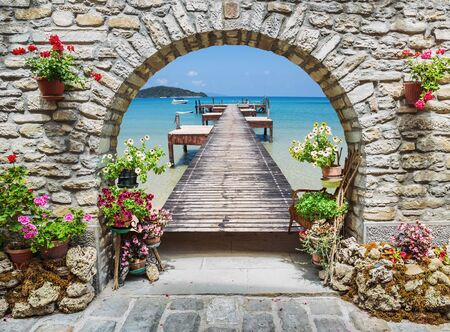 Seaview through the stone arch with flowers in Italy