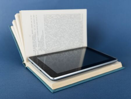 e reading: Modern ebook reader in traditional book  on a blue background