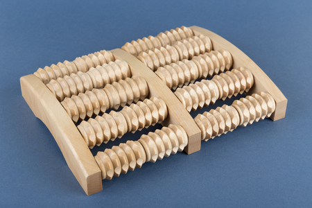 traditional healer: Wooden roller massage tool  for feet on a blue background