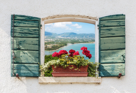 Uitzicht op zee door het open raam met bloemen in Italië Stockfoto