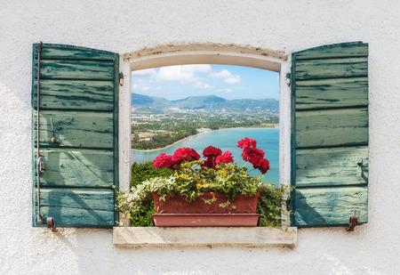 paisaje mediterraneo: Vista al mar a través de la ventana abierta con flores en Italia Foto de archivo