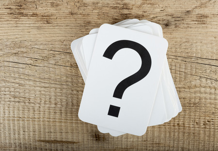 questions: Stack of cards with a question mark on the old wooden background