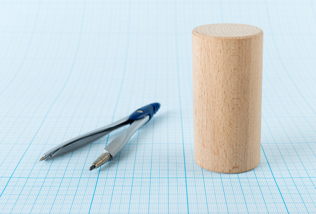 three dimensions: Wooden geometric shape cylinder on graph paper