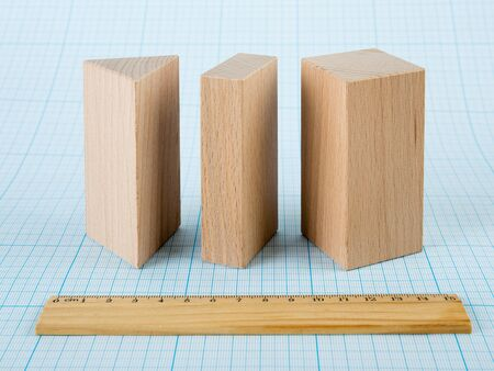 cuboid: Wooden geometric shapes on graph paper Stock Photo
