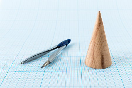 graph paper: Wooden geometric shape cone on graph paper Stock Photo