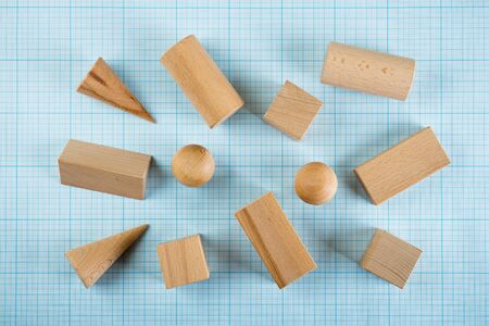 three dimensions: Wooden geometric shapes on graph paper Stock Photo
