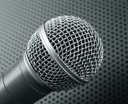 perforated: Classic dynamic microphone on black background perforated. Toned Stock Photo