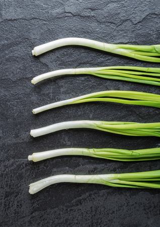 green onions: Green onions on a black stone table