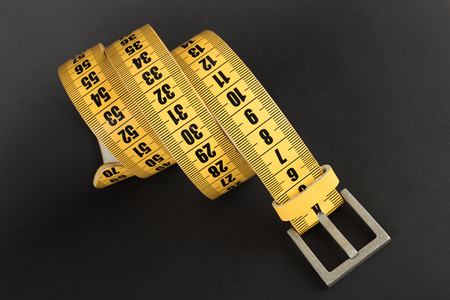 fat and slim: Yellow meter belt slimming on a black Stock Photo