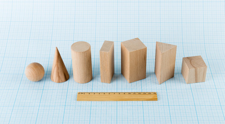 Wooden geometric shapes on graph paper Stock Photo