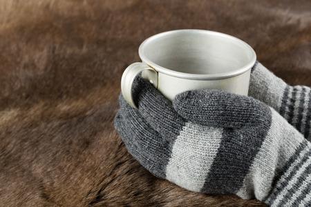keep: Hands in knitted gloves keep aluminum mug