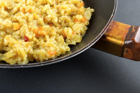 teflon: Boiled rice in a Teflon frying pan on a black background