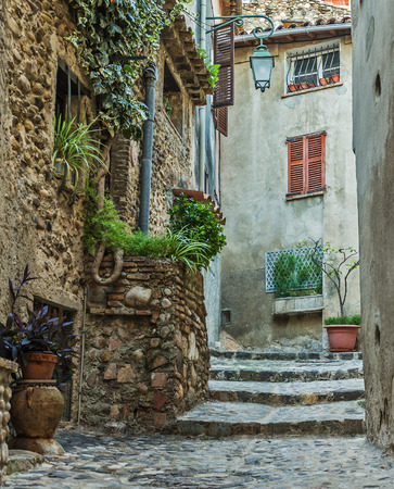 french doors: Narrow street with flowers in the old town  in France.
