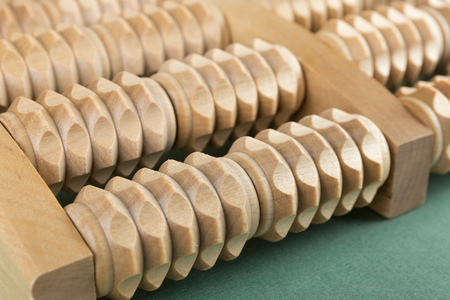 traditional healer: Wooden roller massage tool  for feet on a green background Stock Photo